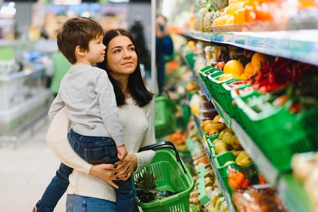 ファーマーズマーケットで果物を買う母と息子