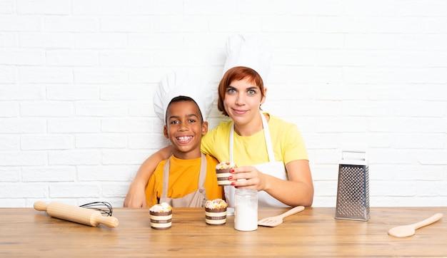 Мать и ее сын, одетый как шеф-повар на кухне
