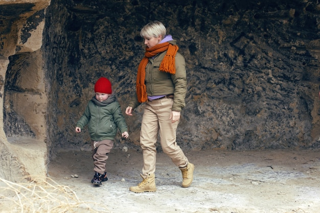 Мать и сын путешествуют по пещерам в теплой одежде.