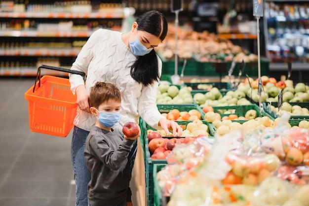 코로나 바이러스 전염병 동안 슈퍼마켓에서 얼굴 보호 마스크 가게를 착용 한 어머니와 아들