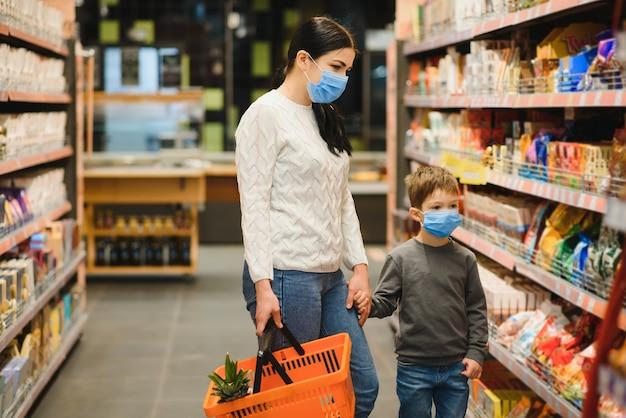 슈퍼마켓에서 얼굴 보호 마스크 가게를 입고 어머니와 그녀의 아들