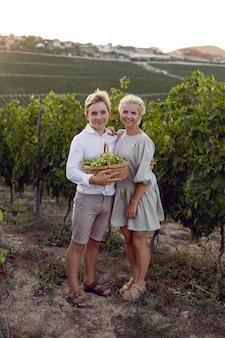 母と彼女の10代の息子は、自然の中で籐のバスケットと緑のブドウとブドウ園に立っています