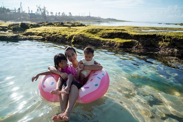 母と2人の子供がブイリングに乗っているときに笑う