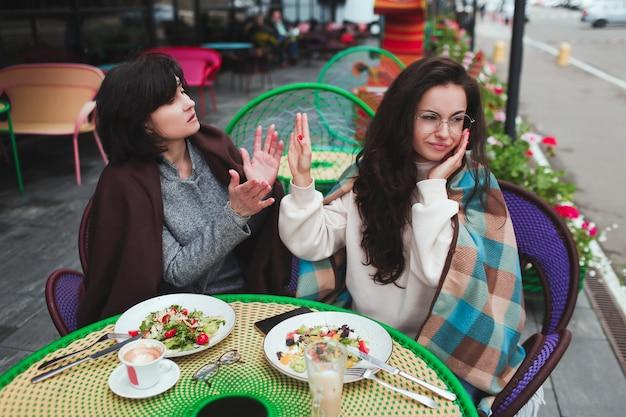 母と彼女の若い娘がカフェで一緒に座る