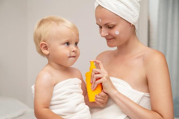 흰 수건에 엄마와 유아 아기가 선 스크린을 바르거나 선 로션이나 크림을 바릅니다. 어린이 스킨 케어