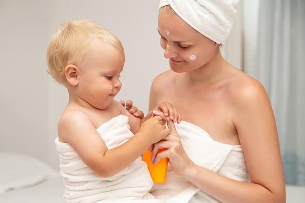 흰 수건에 엄마와 유아 아기가 선 스크린을 바르거나 선 로션이나 크림을 바릅니다.