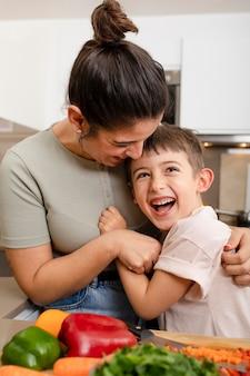 Мать и ребенок обнимаются на кухне