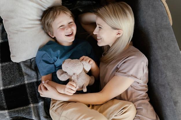 ソファの上におもちゃを持つ母と子