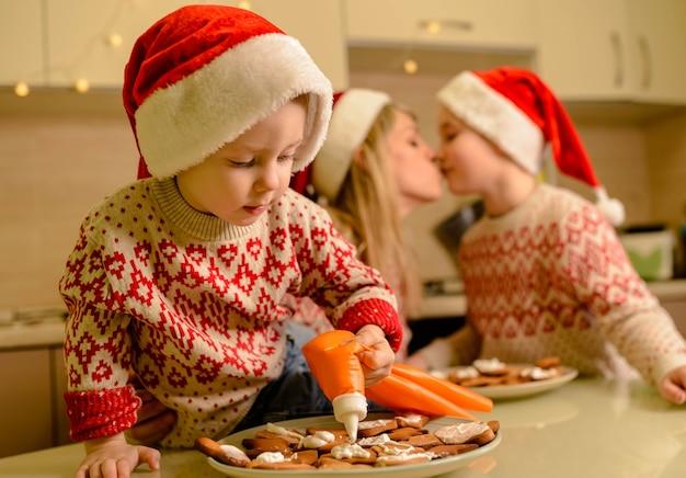 クリスマスにジンジャーブレッドクッキーを作る母と子