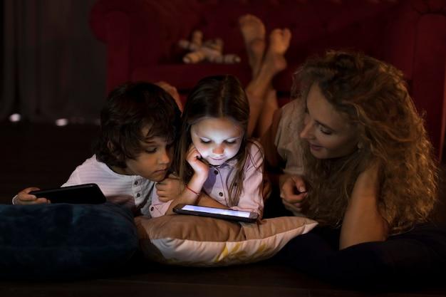 母とタブレットで一緒に遊ぶ子供たち