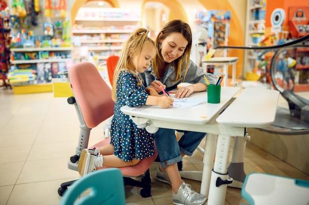 엄마와 어린 아기가 아이의 가게에 그립니다. 어린이 가게의 쇼케이스 근처 엄마와 사랑스러운 소녀