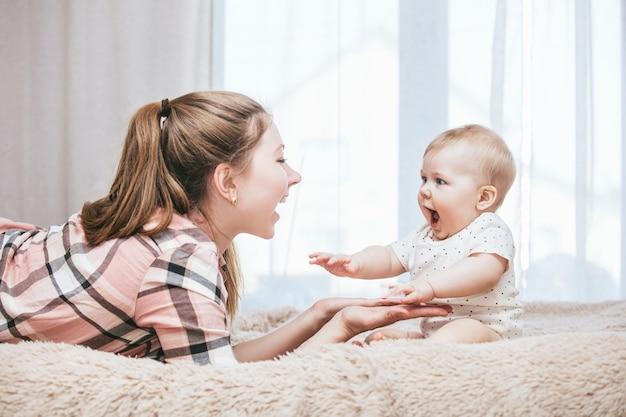 Мать и маленький ребенок в постели и проснулись утром и улыбаются дома