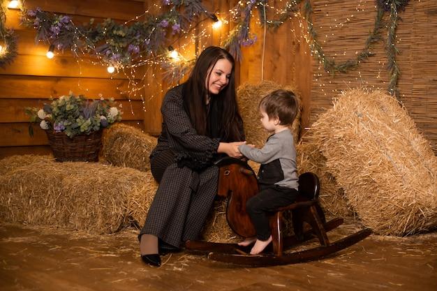 母親と小さな赤ちゃんわらの束を持つファームのおもちゃの馬に座っています。
