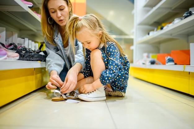 엄마와 아이의 가게에서 신발에 노력하는 작은 아기
