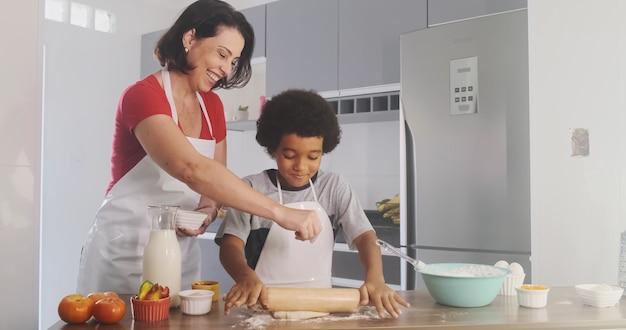 반죽을 준비하는 엄마와 어린 소년 부엌과 주니어 셰프 컨셉의 행복한 가족