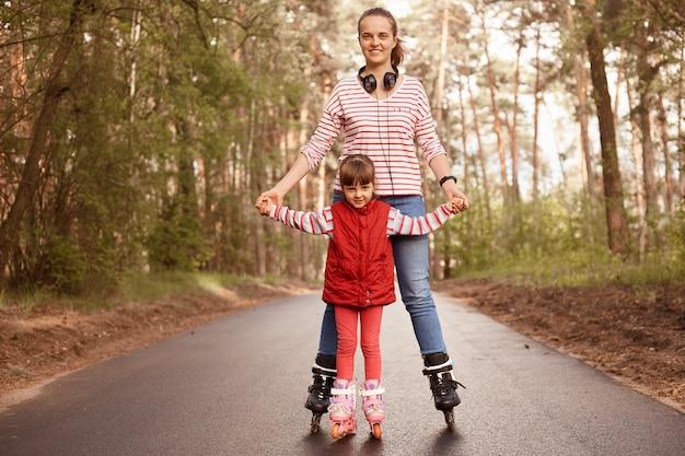 Мать и маленькая очаровательная дочь играют в лесу, катаются на роликовых коньках