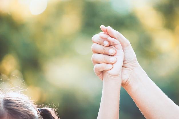母親と小さな子供の女の子一緒に公園で育った手を保持