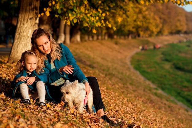 Мать и дитя играют с собакой среди осенних листьев
