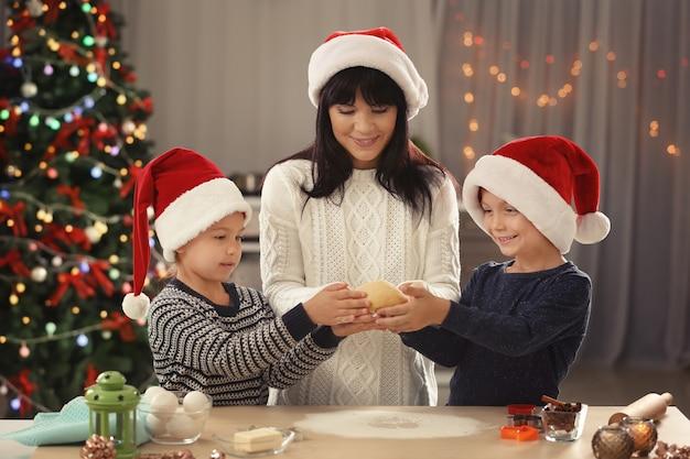 부엌에서 크리스마스 쿠키를 만드는 어머니와 어린 아이들