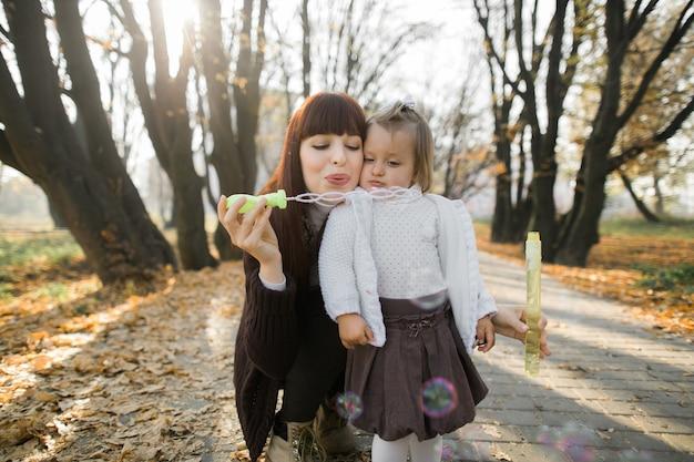 Мать и маленькая милая дочь играют вместе с мыльными пузырями