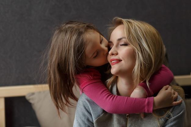 母と幼い娘がベッドで遊んで抱きしめています。幸せな母性。