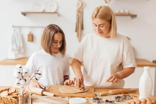 Мать и дочка пекут печенье и веселятся на кухне