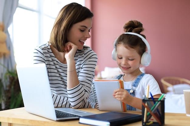オンラインで宿題をしている母と娘。遠隔教育オンライン教育。