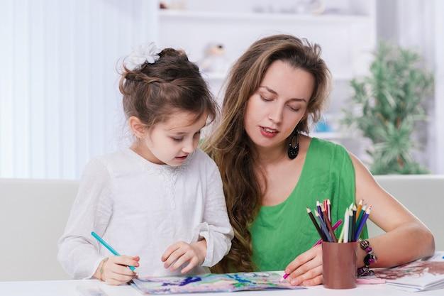 어머니와 어린 딸이 테이블에 그림을 그립니다. 어린이 창의력의 개념