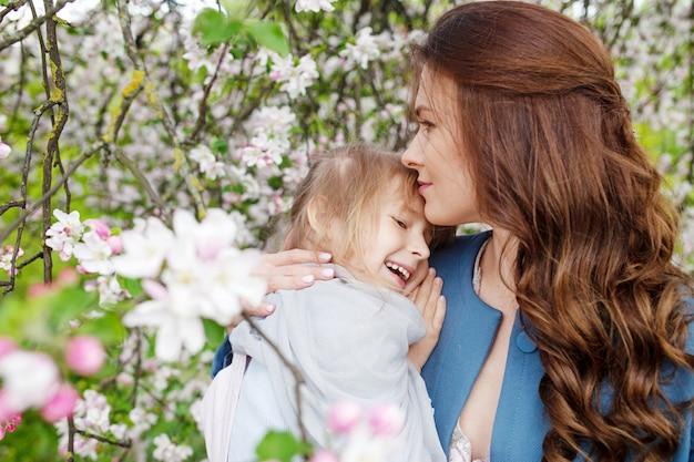 Мать и маленькая дочь обнимают друг друга и гуляют в цветущем яблоневом саду. мама любит своего ребенка. весенняя история. счастливая семья в прекрасный весенний день