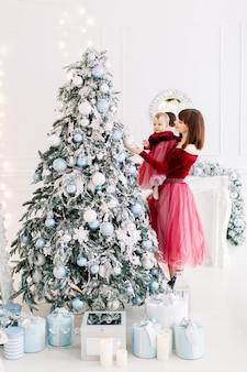엄마와 빨간 드레스에 작은 딸, 아름다운 크리스마스 트리 장식