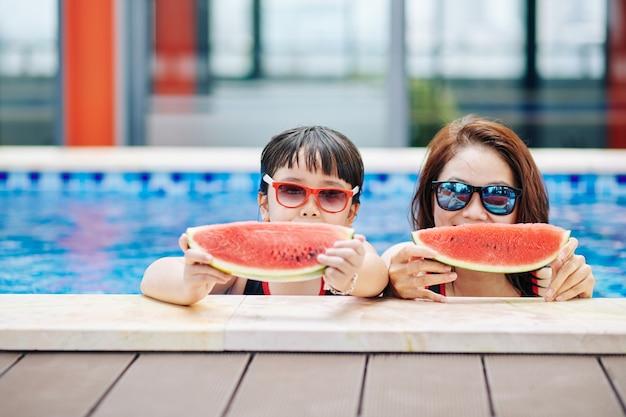 サングラスをかけた母と娘がプールに立って、甘いおいしいスイカのスライスを食べる