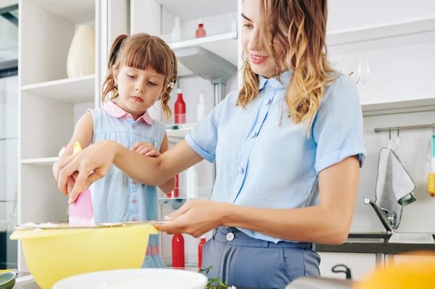 Мать и дочка смешивают ингредиенты теста для печенья в большой пластиковой миске