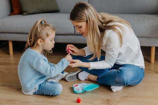 Мать и дочка красят ногти игрушечным лаком для ногтей