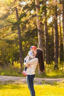 秋の公園で一緒に遊んでいる母と娘。