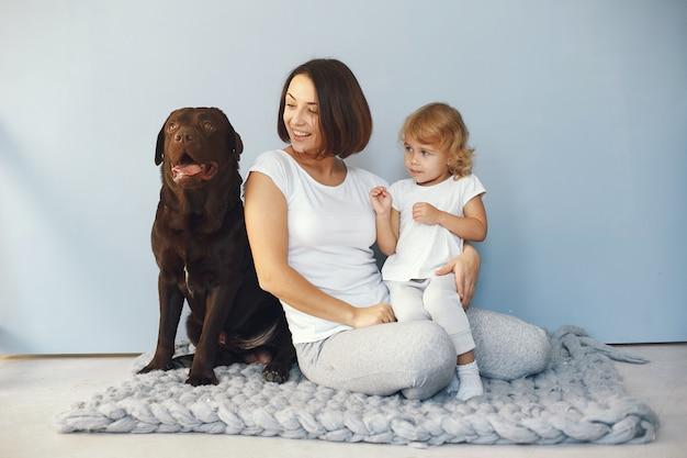 Мать и маленькая дочь, играя с собакой дома