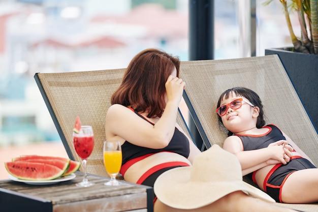 スイミングプールのそばの長椅子で日光浴をし、フルーツカクテルとスイカのスライスを楽しむ母と娘