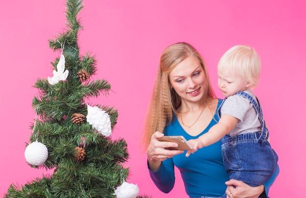 クリスマスツリーの近くで自分撮りをしている母と娘