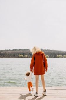 湖のほとりの木の桟橋を歩く母と娘