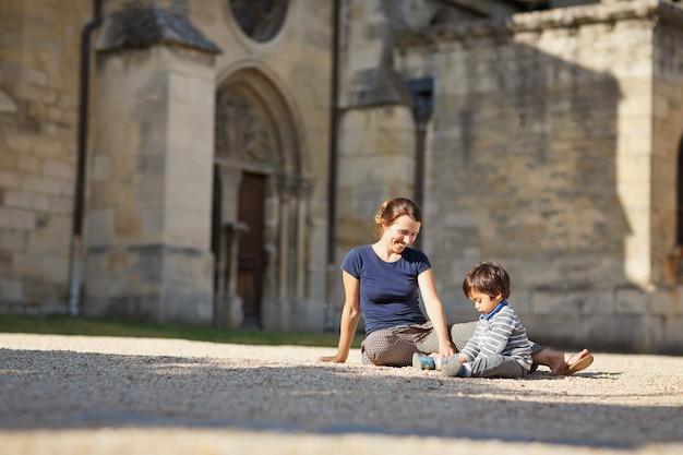 公園で屋外で遊んでいる母と小さな東部のハンサムな男の子。ヨーロッパのコンセプトで幸せな混血家族