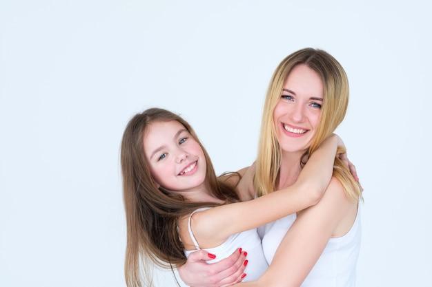 어머니와 어린 소녀 포옹. 행복한 부모 자녀 관계.