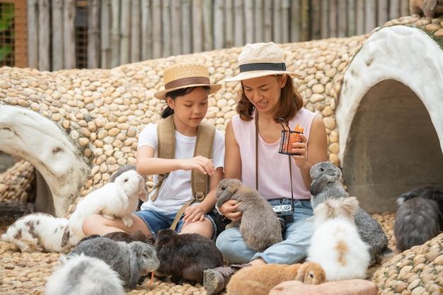어머니와 어린 소녀 먹이와 토끼를 쓰다 듬.