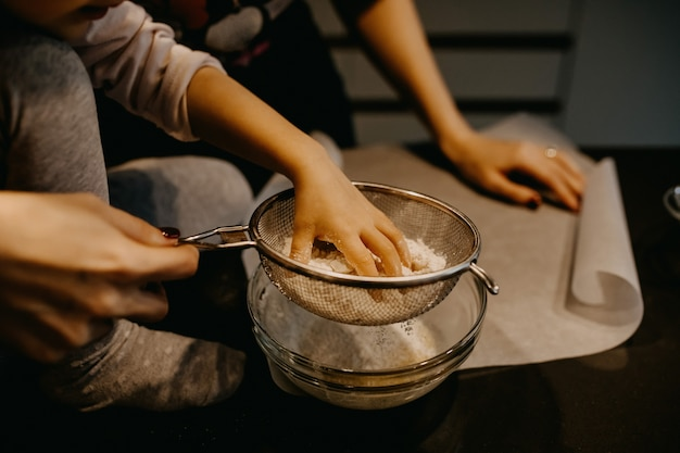 Мать и маленькая девочка наливают муку в миску, делая тесто для печенья