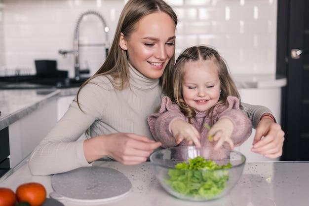 母と少女がサラダを準備するキッチンで野菜をスライス