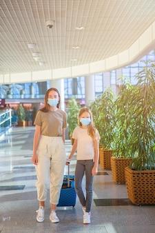 母と空港でのネディカルマスクを持つ少女。コロナウイルスに対する保護