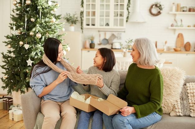 ソファに座って、リビングルームでクリスマスに長女に暖かいスカーフを与える母と妹