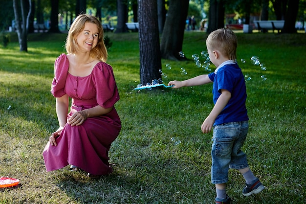 母と幼い息子が泡で遊んで庭で笑う