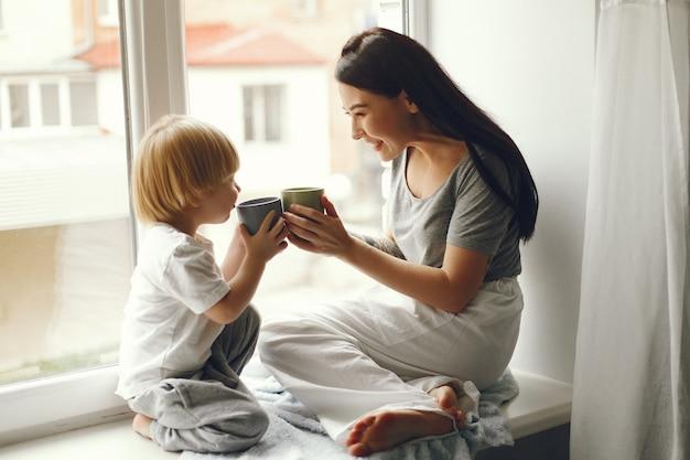 Мать и маленький сын сидят на подоконнике с чаем