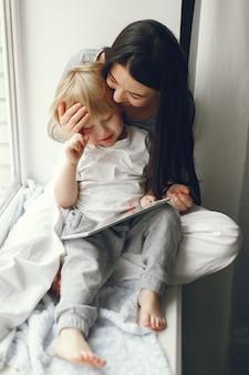 Мать и маленький сын, сидя на подоконнике