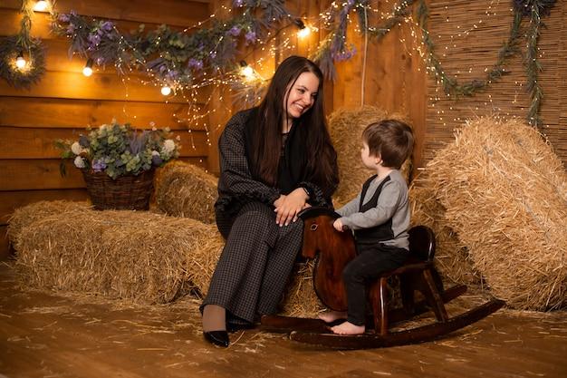 母と幼い息子のわらの束を持つファームのおもちゃの馬に座っています。