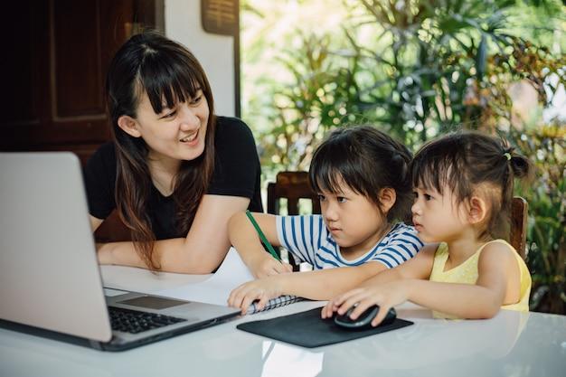 집에서 공부를 위해 노트북을 사용하는 어머니와 유치원 딸.